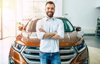 handsome man smiling standing near new modern car in dealership, buying car concept