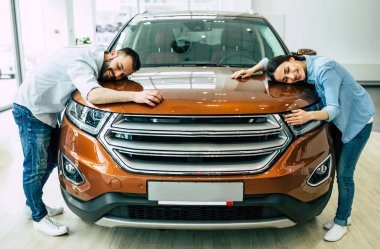 Happy young couple in casual wear hugging hood of new car in dealership, buying car concept