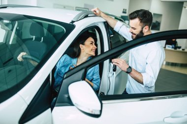 Happy woman sitting in new car and man giving her key in dealership, buying car concept