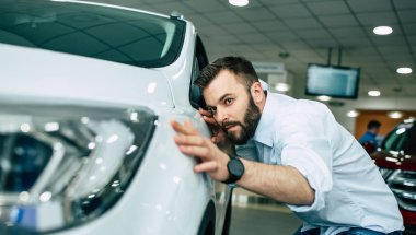 happy smiling man checking hood of new car in dealership