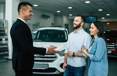 car salesman in dealership telling young customers about stock in store. buying car concept
