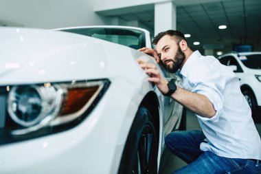 Confident man choosing car in dealership