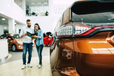 Happy young couple choosing and buying new car visiting dealership
