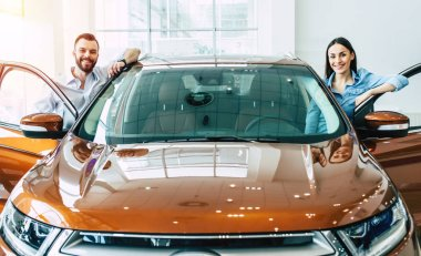 Happy young couple in casual wear standing near new car in dealership, buying car concept