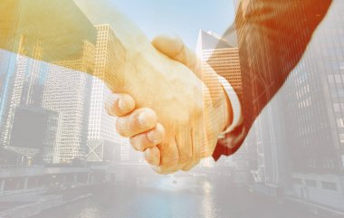 handshake of two businessmen with cityscape background
