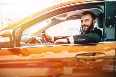 Good and comfortable wheel. Confident man inspecting car design buying car dealership