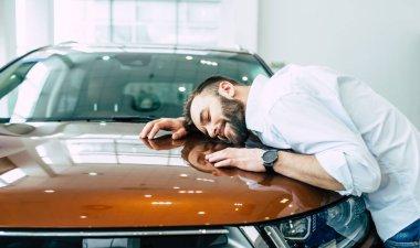 happy smiling man hugging hood of new car in dealership