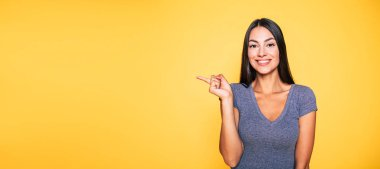 Portrait of smiling brunette gesturing with finger on yellow background