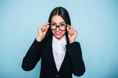 Portrait of young businesswoman fixing glasses on blue background