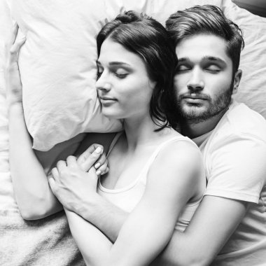 Young heterosexual couple cuddling on bed