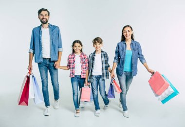 young caucasian family with shopping bags on white background, shopping concept