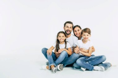 Group portrait of young caucasian family with son and daughter on white background