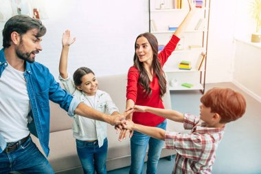 Friendly young family gathering hands together in circle