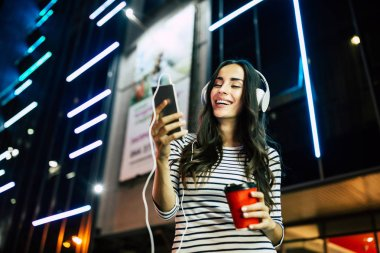 Young smiling woman listening to music in headphones with smartphone