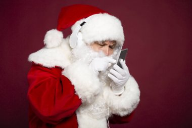portrait of man in Santa Clause costume holding smartphone and listening to music at headphone on red background, Christmas and New year concept