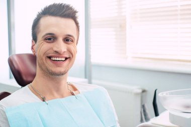 Ace it! Man  in the dental chair  with a dental napkin over his chest who is happy and pleased because of his appointment and a treatment in the dentist cabinet of a professional clinic.
