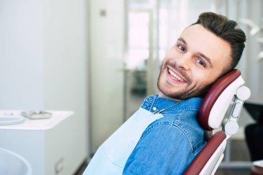 Draw the eye. A man is smiling while having a qualified dental treatment in a professional clinic. He is absolutely relaxed and it can be seen from his facial gesture and shine in his eyes.