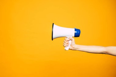In a bull voice. A yellow background with a female hand in front of it holding three colored megaphone of white, black and blue colors.