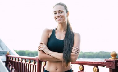 Sport, Healthy lifestyle, Yoga, Pilates, Jog. Attractive young sporty woman in sportswear in good mood is doing morning stretching exercises on the city bridge outdoors