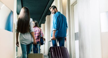 Beautiful happy excited family with a backpack and suitcases in modern hotel
