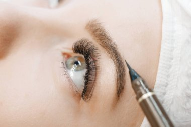 close up of woman at procedure for eyebrows shape forming in beauty salon