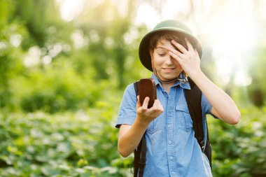 portrait of little boy with compass exploring summer forest