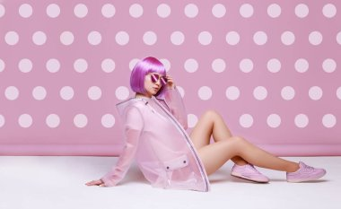 Beautiful woman with purple hair in fashionable clothes and glasses posing on pink polka dot background.