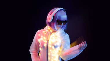 Beautiful woman with purple hair in futuristic costume and glasses over dark background. Blue and violet neon light. Portrait of young girl in modern headphones listening music. Free space for text.