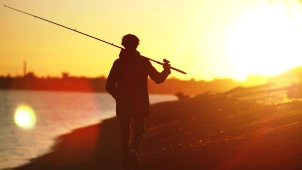 Střílí se pomalu. Silueta rybáře na pozadí podzimního západu slunce