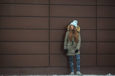 Portrait of a young pretty caucasian teenage girl in a blue hat, black gloves and a green jacket with a hood in the winter outside.