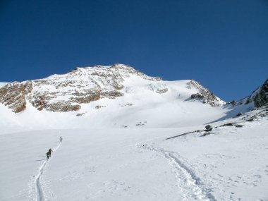 several backcountry skiers crossing a large alpine glacier on their way to a remote mountain peak under a blue sky in winter