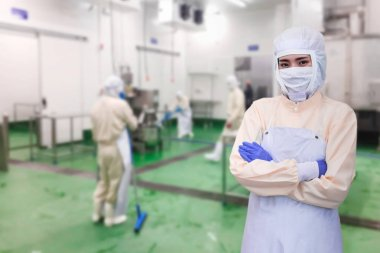 White protective uniform with mask and gloves. Quality control worker jobs washer in food industrial process, Cleaning floor in food plant, Young female supervisor.