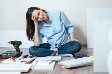 Tired young woman sitting on the floor in front of furniture items