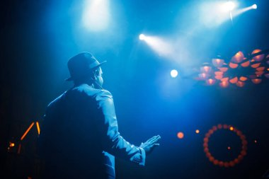 Dark-skinned singer in a suit and hat on a stage illuminated by blue light. Hight quality photo