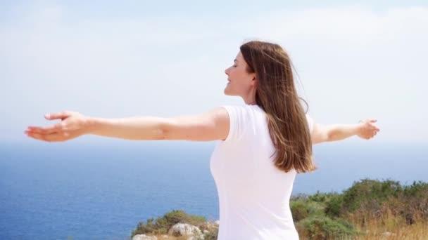 Žena na útesu proti modré moře zvedni ruce. Ženské traveleer outstretching ruce v pomalém pohybu