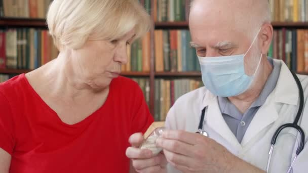 Male professional doctor at work. Senior man physician treat senior female patient giving flu pill