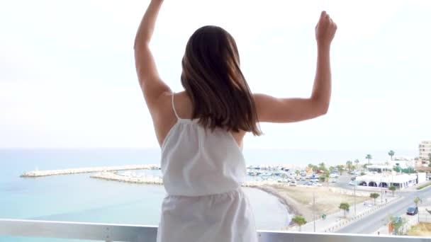 Woman jump with joy on terrace with sea view. Silly female raise arms up and dance in slow motion