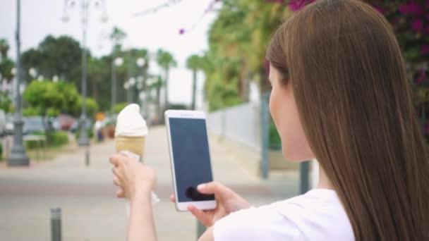 Žena pořizování Foto kužel zmrzliny. Teenagery fotografování zmrzliny na fotoaparát telefonu ve zpomaleném záběru