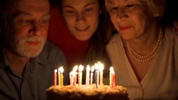Milující starší pár a jejich dcera slaví s dortem doma. Objímání a foukání svíčky