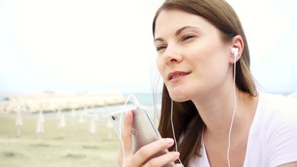 Young smiling woman using mobile on beach alone. Female listening music via cellphone in slow motion