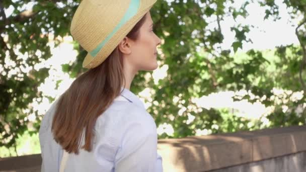 Woman walk along waterfront in slow motion. Behind view of female traveler enjoying vacation outdoor