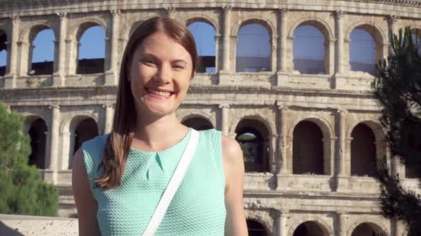 Young woman near famous attraction Colosseum in Rome, Italy. Female tourist smiling in slow motion
