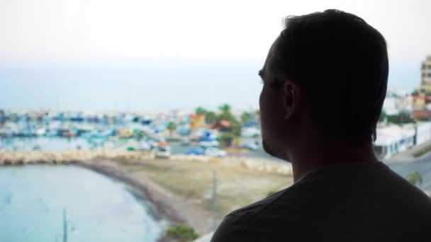 Silhouette of man enjoying sea view from terrace. Male traveler looking at marina from balcony
