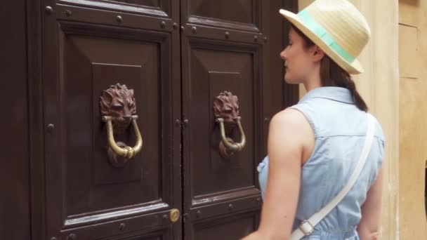 Woman near old wooden door hold handle in form of lion. Female traveler knock on door in slow motion