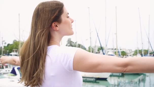 Young woman standing alone on pier. Inspired carefree female raising her arms up in slow motion