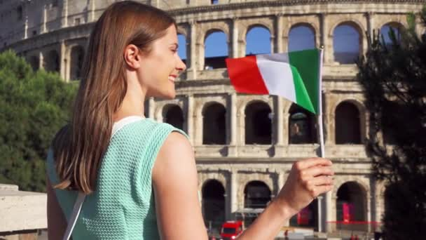 Young woman standing near Colosseum in Rome, Italy. Teenage girl waving Italian flag in slow motion