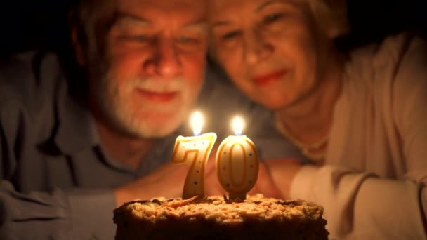 Loving senior couple celebrating anniversary with cake at home in the evening. Blowing out candles.