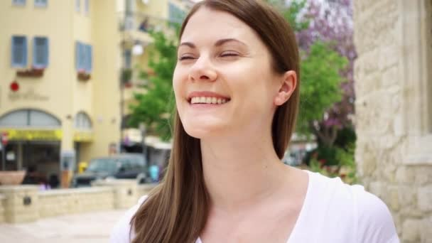 Smiling young woman in white t-shirt walk down street in european city in slow motion. Looking around