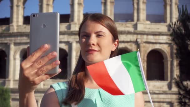 Woman do selfie on mobile near Colosseum in Rome, Italy. Teenager wave Italian flag in slow motion