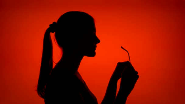 Silhouette of woman putting on glasses on red background. Female face in profile with eyeglasses